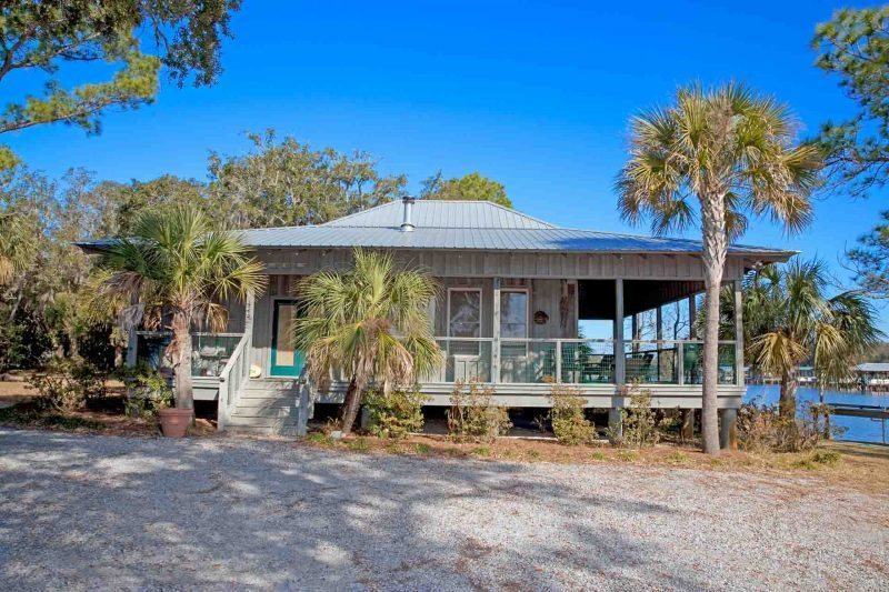 Side profile Fishing style cottage with wrap around cover porch on Florida bayou.