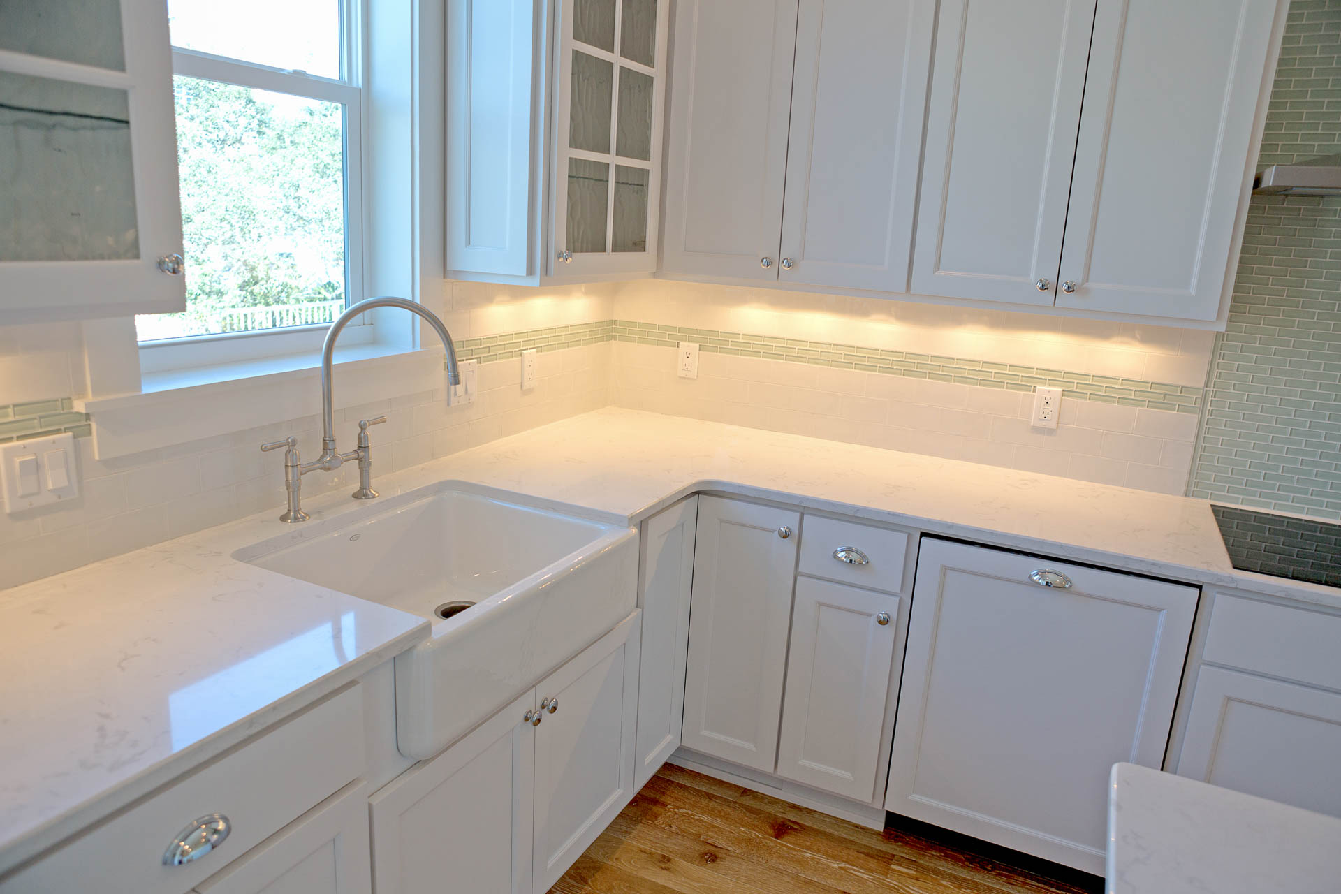 High end kictchen with white granite, farm house sink, and light green back splash inside new construction home in Old Florida Beach on 30A.
