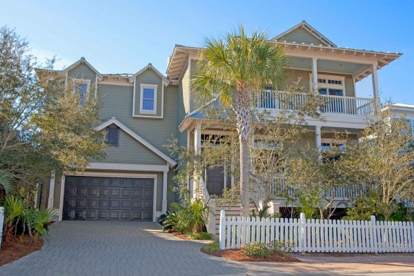 Road side view of two story new custom beach home with two car garage in Old Florida Beach subdivision on 30A.