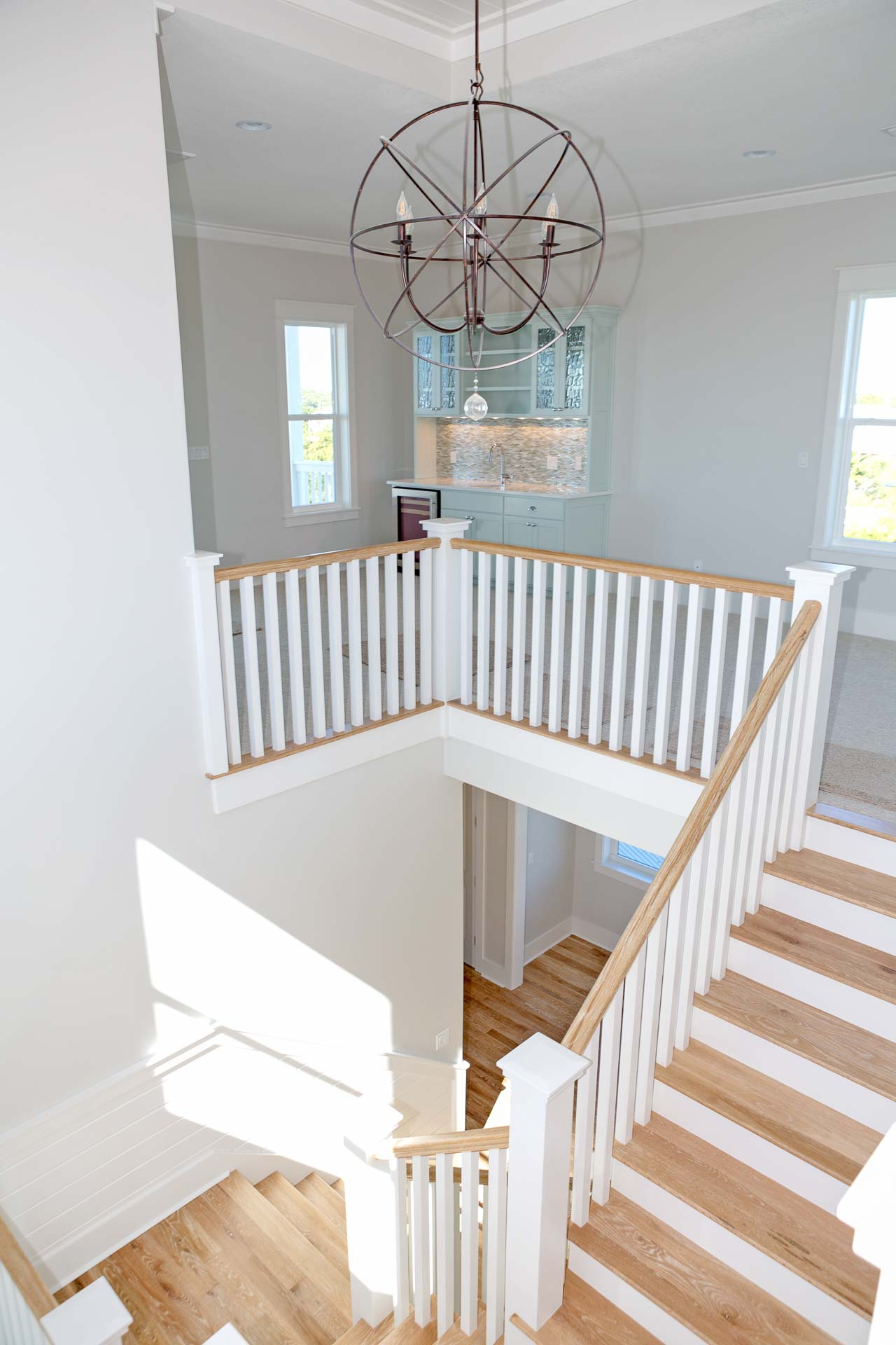 Stair case with hard wood floors and globe light fixure inside newly built custom home in Old Florida Beach on 30A.