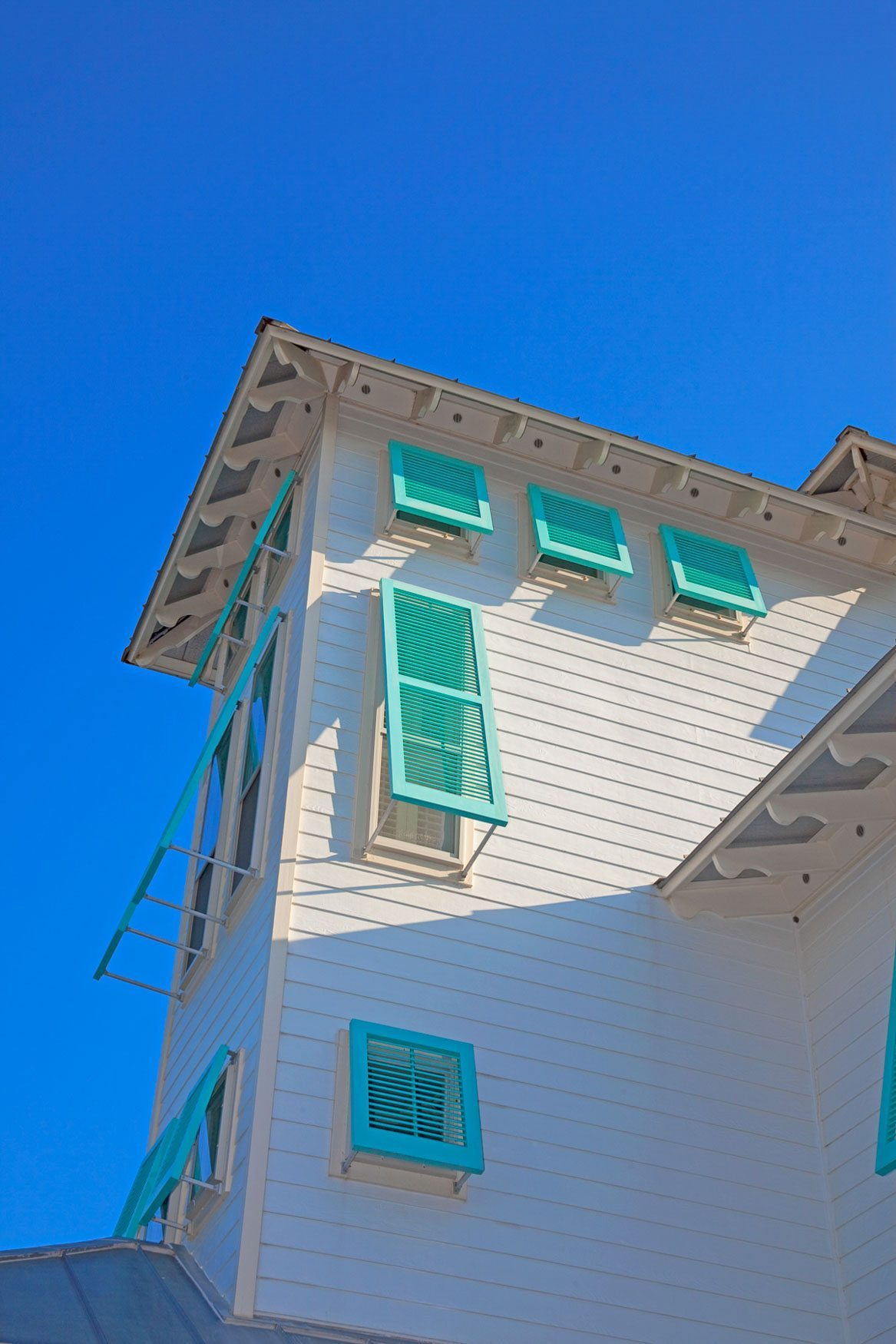 Side of three store house showing teal color bahama shutters in Old Florida Beach on 30A.